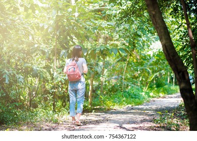 hipster woman traveler with backpack holding map at nature backgrounds park garden yard outdoors