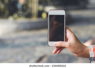 hipster woman using mobile phone touching screen at outdoor with hands typing smart phone texting messaging lifestyle working app device technology internet social data online concept vintage style.
