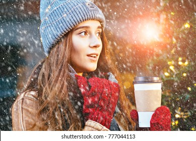 Hipster woman in warm clothes, red mittens with disposable cup of coffee outdoor in city street. Snowfall and sun glare effect. Wonder emotion fairytale and christmas concept. Close up