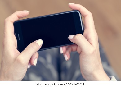 Hipster woman's hands are holding a smartphone.