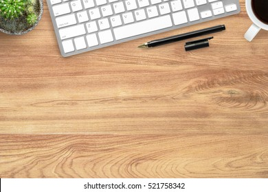 Hipster wood office desk table with computer keyboard, pen and coffee cup. Top view with copy space, flat lay.