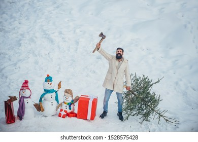 Hipster woodsman with Christmas tree. Man is going to cut a Christmas tree. Christmas tree cut. Bearded Man cutting Christmas tree