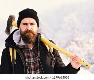 Hipster woodsman concept. Macho in winter clothes with backpack and yellow ax. Man with beard and mustache holds axe. Guy with sad face with snow on background.