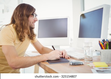 Hipster working on graphics tablet at computer desk in office