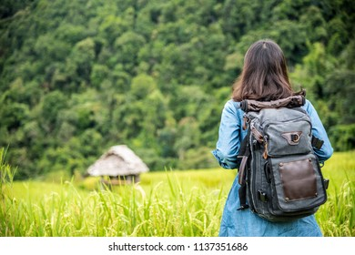 Hipster young Asian girl traveller with backpack standing in the field or paddy landscape, happy travel holiday.