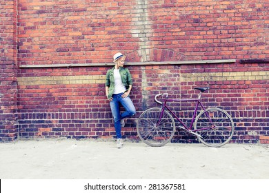 Hipster young beautiful girl with vintage road bike in city, urban scene. Beauty woman cycling on fixed gear bike in town, retro city street industrial background.