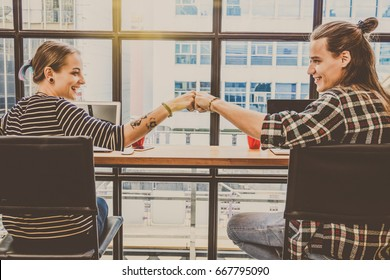 Hipster young couple freelancer Fist Bumping Corporate Colleagues Teamwork in the Loft cafe workplace. Creative Startup and entrepreneur business concept