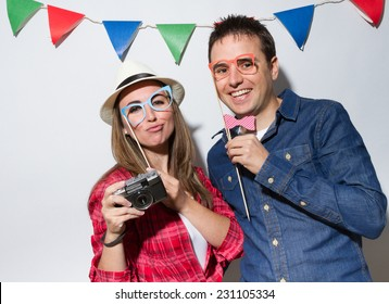 Hipster young couple in a Photo Booth party