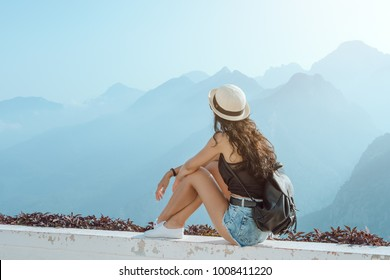 Hipster young girl with backpack enjoying sunset on peak of mountain. Tourist traveler sitting on viewing platform of hotel agaist blue background valley landscape view mockup for text. Attractive