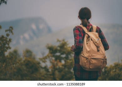Hipster young girl with backpack enjoying sunset on peak of foggy mountain. Tourist traveler on background view mockup.
