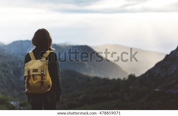 Hipster young girl with backpack enjoying sunset on peak mountain. Tourist traveler on background valley landscape view mockup. Hiker looking sunlight flare in trip in Spain basque country Europa