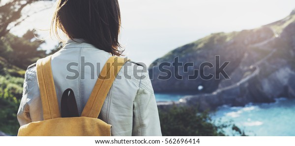 Hipster young girl with backpack enjoying sunset on seascape on peak mountain. Tourist traveler on background valley landscape view mockup. Hiker looking ocean in trip holiday in basque island