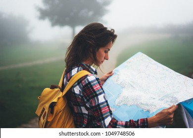 Hipster young girl with backpack holding in hands looking on map spain of foggy mountain, tourist traveler hiker on background valley landscape panoramic view, trip in northern spain basque country