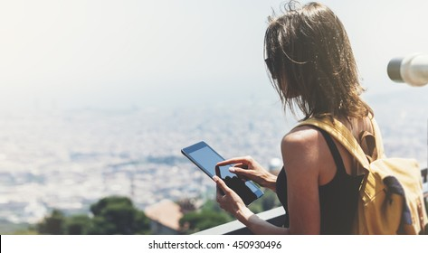 Hipster young girl with  backpack. Tourist traveler on background panoramic view of the city, coin binoculars. Mock up for text message. Barcelona Tibidabo. Female hands using tablet, holding gadget