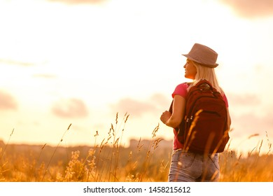 Hipster young girl with bright backpack enjoying sunset on peak of foggy mountain. Tourist traveler on background valley landscape view mockup. Hiker looking sunlight flare in trip