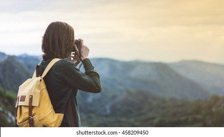 Hipster young girl with bright backpack taking photo of amazing landscape sunset on vintage camera on peak mountain mockup. Tourist traveler on background sunlight in trip in northern Spain