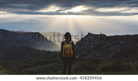 Hipster young girl with bright backpack enjoying sunset on peak of foggy mountain. Tourist traveler on background valley landscape view mockup. Hiker looking sunlight in trip in northern Spain