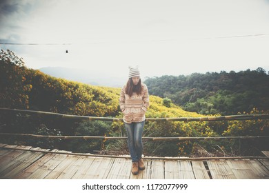 Hipster young girl enjoying on peak of foggy mountain, Landscape Mexican sunflower Tung Bua Tong at Doi Hua Mae Kham in Chaing Rai, Thailand.