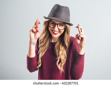 Hipster young girl with her fingers crossing