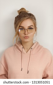 Hipster young girl making duckface over wall. Portrait of a cute positive seductive fashion model in street style having fun posing indoors. Beautiful blond woman wearing pink hoody and stylish