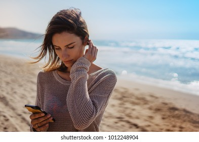 Hipster young girl photograph on smart phone gadget in sand coastline, traveler hold and using in female hand mobile screen on background seascape horizon, tourist look on blue sun ocean, lifestyle