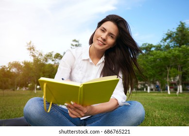 hipster young girl reading notebook and makes notes with pen while sitting in the park on green grass. Female person spending recreation time with literature