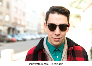 Hipster young male on the street looking straight to the camera. Warm colors, blurred background