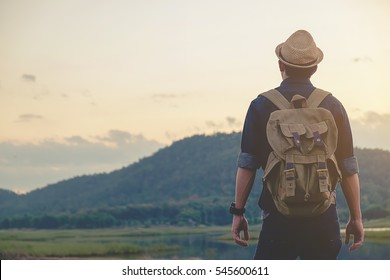 Hipster young man with backpack enjoying sunset on peak mountain. Tourist traveler on background valley landscape view mock-up.Retro filter effect, selective focus.