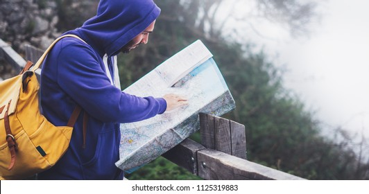 Hipster young man with backpack holding in hands and looking on map spain of foggy mountain, tourist traveler hiker on background valley landscape panoramic view, trip in northern spain basque country