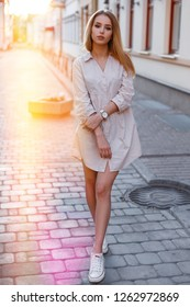 Hipster young woman in a trendy summer pink dress in white sneakers is standing on an old street in the city on the background of a bright orange sunset. Charming girl.
