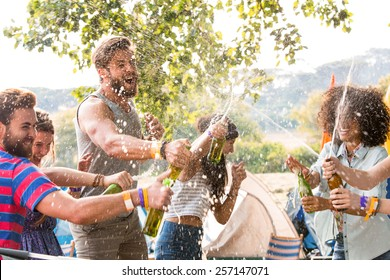 Hipsters spraying beer over each other on a sunny day