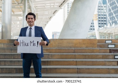 Hire me! Handsome businessman wear blue suit holding poster with hire me text message while standing outdoors and against building structure