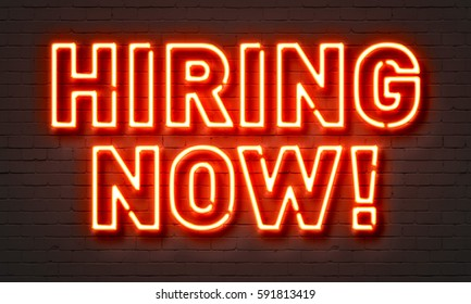 Hiring now neon sign on brick wall background
