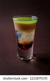 Hiroshima alcoholic shot glass with absent, sambuca, irish cream on elegant dark brown background.