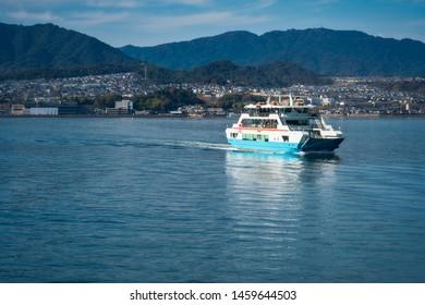 Hiroshima Bay, Japan - November 7, 2018: View of an afternoon boat ride (ferry) on the ocean to the UNESCO World Heritage Site, the shrine island of Miyajima (Itsukushima) in Japan, near Hiroshima bay
