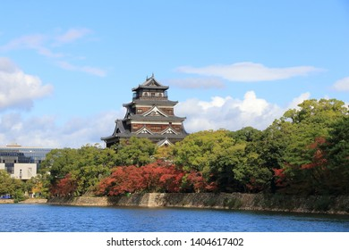 Hiroshima Castle, The Carp Castle, the moat for sightseeing boat, and red autumn maple leaves in Hiroshima Japan under a sunny blue sky. Destroyed by an atomic bomb and rebuilt in 1958.