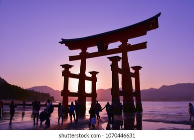 HIROSHIMA, JAPAN - APRIL 3, 2017: The great O-Torii of Itsukushima Shrine. Tourists walk around the famous tori gate of the Itsukushima Shrine on Miyajima Island during sunset time.