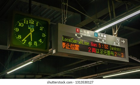 HIROSHIMA, JAPAN - DECEMBER 10, 2016:  A huge rectangular electronic board showing the type of train line, departure time and destination in a typical train station in Japan, with a round analog clock