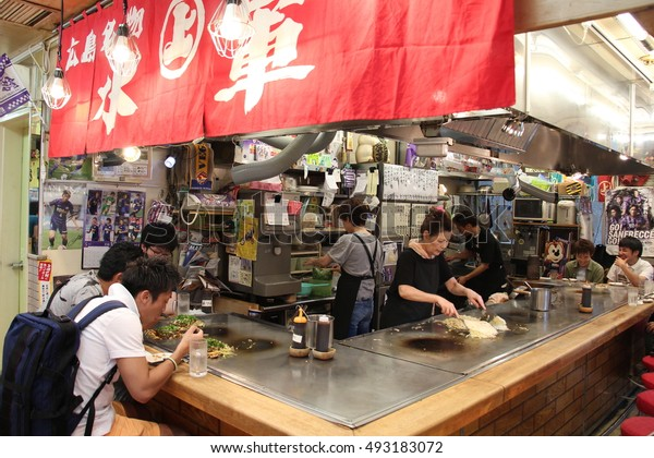 HIROSHIMA, JAPAN - June, 2015 : People eating japan pizza at Okonomiyaki shop in Hiroshima