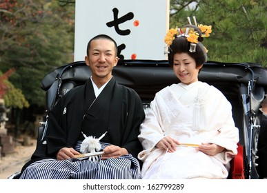 HIROSHIMA - NOVEMBER 15: Unidentified couple dress up in traditonal marriage gowns to celebrate the autumn festival at Miyajima Shrine on November, 15, 2008 in Hiroshima, Japan