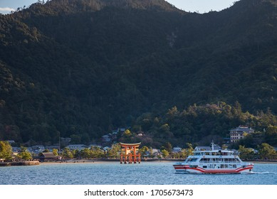 Hiroshima Prefecture, Japan - JAN 02 2019 : Looking at Miyajima island from the ferry. Floating red giant Grand O-Torii gate stands in bay beach at low tide on sunny day, Hiroshima City