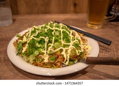 Hiroshima style okonomiyaki (Japanese savoury pancake with multiple toppings) with green onion and mayonaise served with a small spatula