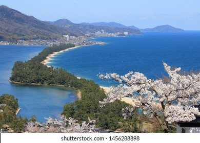 Hiryukan (The flying dragon view) of Amanohashidate, Kyoto, Japan, with full blossom cherry under a blue sunny sky. A pine covered sandbar spans the mouth of Miyazu Bay. Japan's three most scenic view
