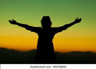 His arms lifted up in the sunset, high energy woman