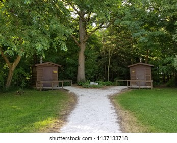 His & hers log cabin style outhouses located in a shaded spot of a rural wooded area in the upper Midwest USA. White gravel footpath & green grass in the foreground. Trees & foliage in the background.