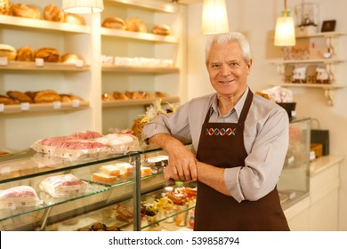 His hobby became his career. Happy senior man smiling leaning on the showcase while working at his own bakery running his small business copyspace
