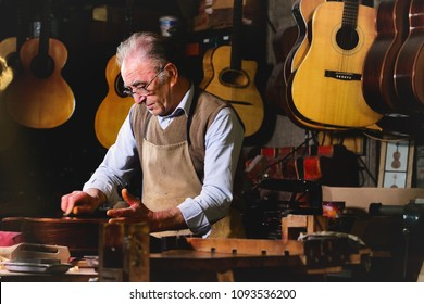 In his laboratory, a liutist builds high quality guitars for musicians, working fine wood. Concept of: music, tradition, ancient crafts.