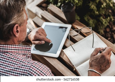 His office in the outdoors. A shot of a mature man sitting back to camera and doing his business outdoors.