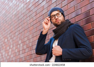 In his own perfect style. Low angle view of handsome young man in smart casual wear adjusting his eyeglasses and looking away while standing against brick wall