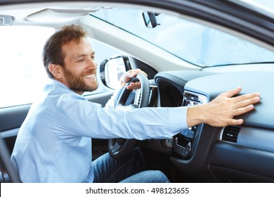 His true love. Portrait of a mature man smiling happily sitting in a brand new car touching the dashboard